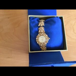 Avon gold based watch with angels on the band .